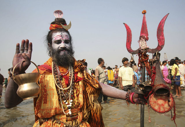 A man dressed as Shiva stands near the confluence of the Ganges River and the Bay of Bengal at Sagar