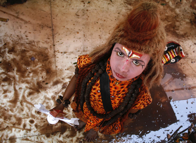 A boy dressed as Lord Shiva stands inside a temple during Mahashivratri festival in Trakeshawar, abo