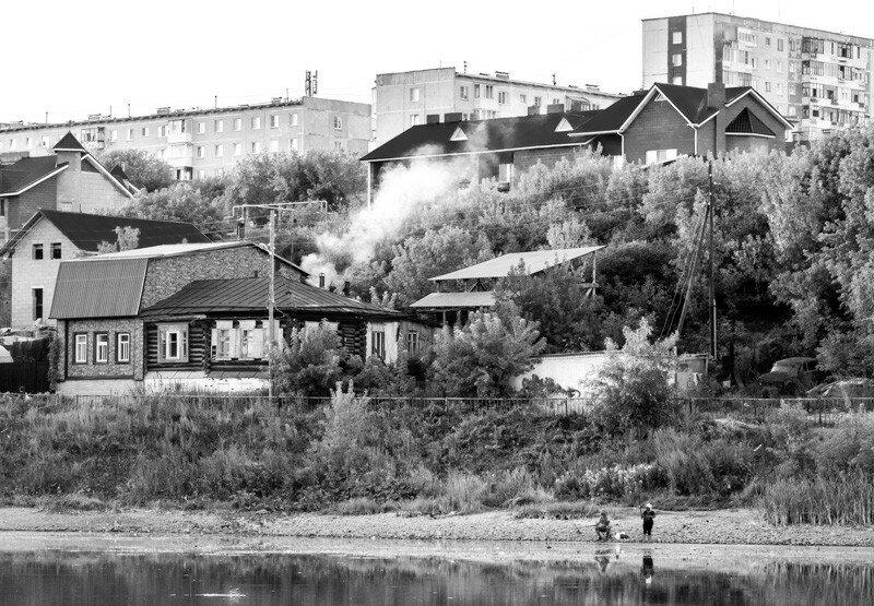 рыбаки отражающиеся в воде, а над ними город
