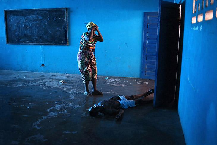 2. Медработник в защитной одежде несет ребенка с подозрением на вирус Эбола, Либерия, 5 октября 2014