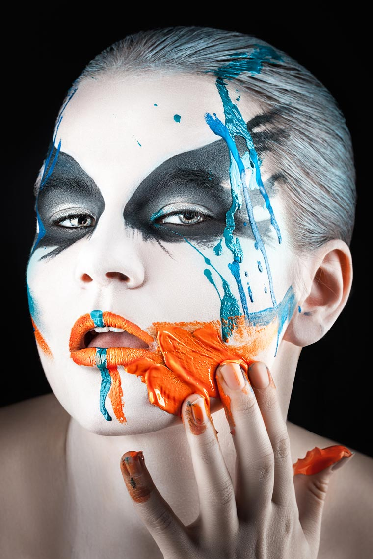 Paint on his face smeared fingers.