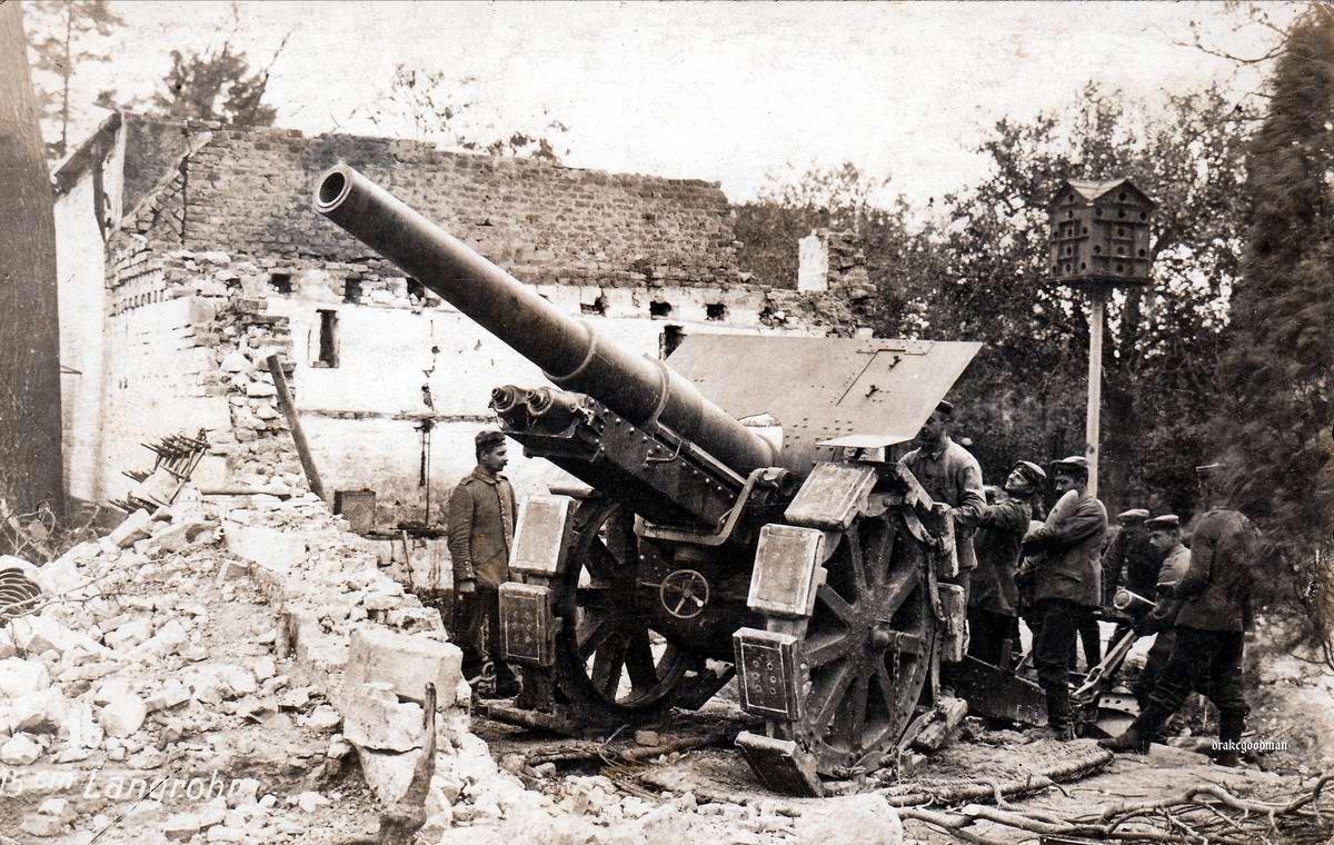 Артиллерийское орудие калибра 13,5 см на боевой позиции среди развалин