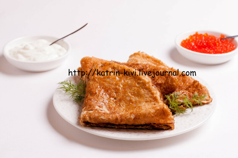 delicious crepes with red caviar, dill and sour cream, isolated on white