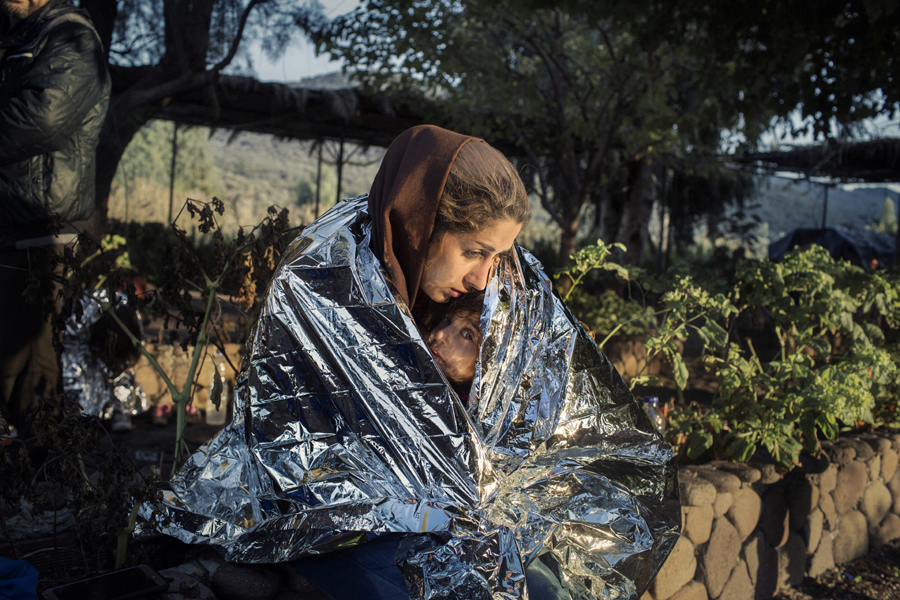 Lesbos, Greece, October 18, 2015. A mother and child wrapped in an emergency blanket after disembark