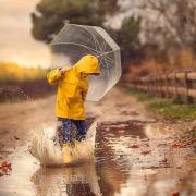 Мальчик бегает по лужам