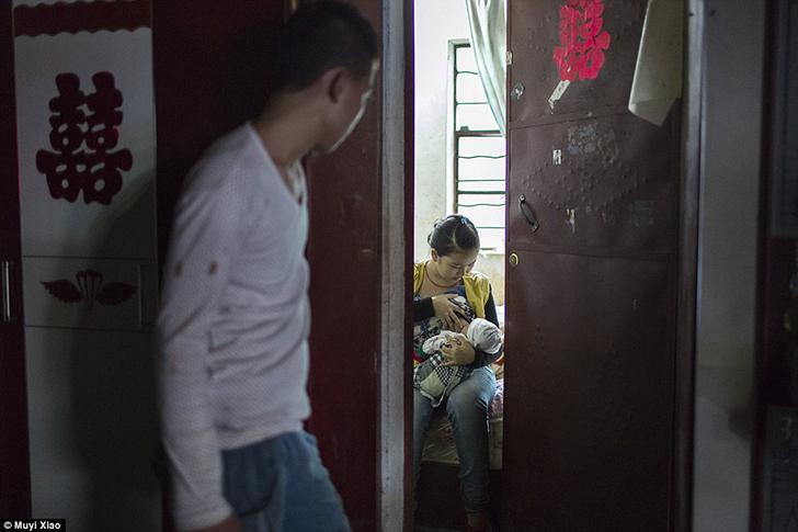 18-летний отец Фан смотрит, как его 16-летняя жена Ли кормит грудью ребенка в спальне их дома.
