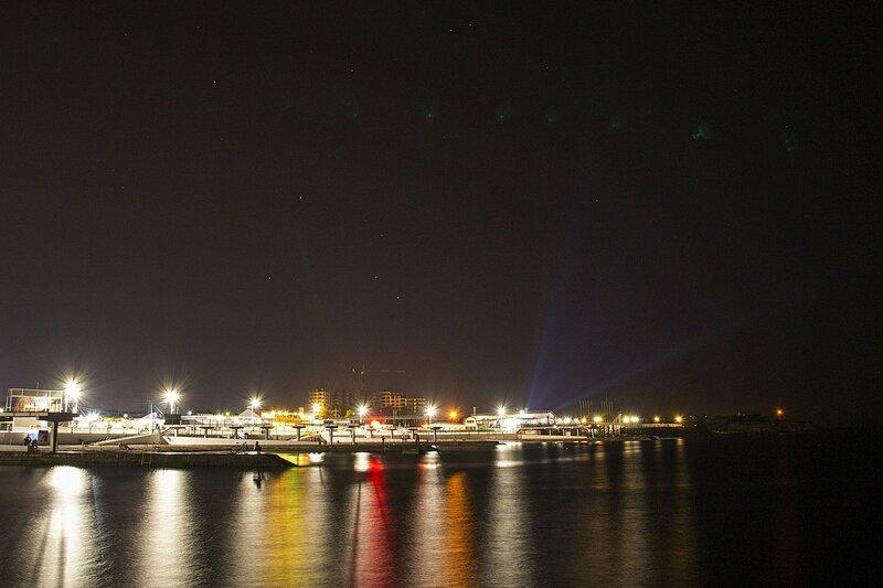 Отражающиеся в ряби волн Чёрного моря ночные огни пляжа парка Победы (Севастополь, Крым)