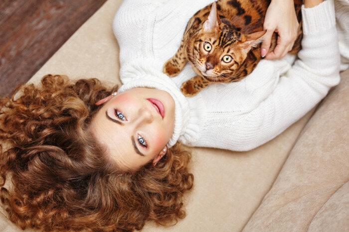 Девушка и бенгальская кошка лежат на диване. Автор фотографии: Елена Вагенджим (Elena Vagengeim).