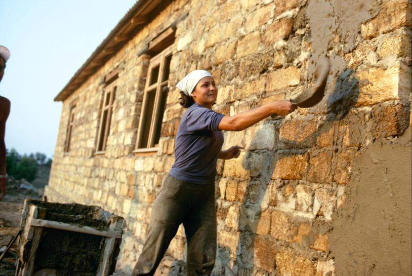 Используя глину, студенты штукатурят дом. Из 45 студентов было всего три девушки. Им доставалась раб