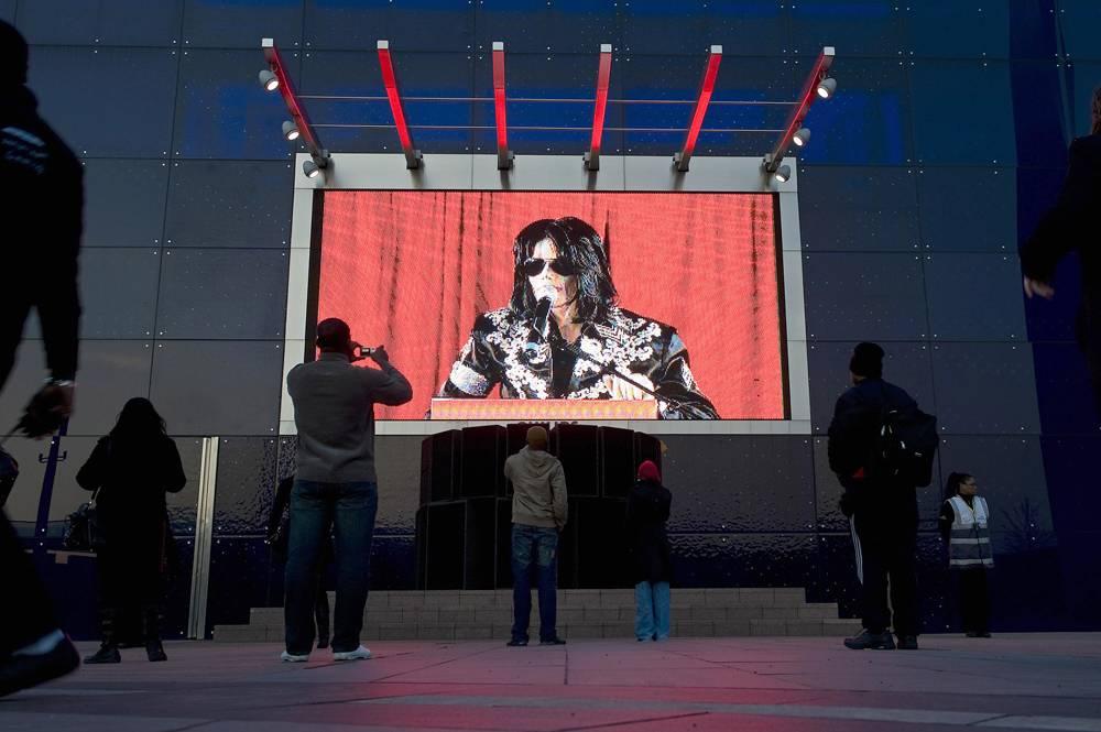 Поклонники смотрят трансляцию пресс-конференции певца на Арене O2 в Лондоне 5 марта 2009 года. В пре