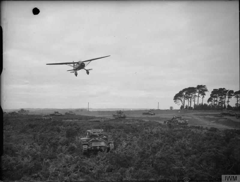 "An RAF Lysander aircraft from Army Co-operation Command flies low over Valentine tanks during an exercise, 18 November 1941. The tanks are marked with crosses to indicate ""enemy"" vehicles."