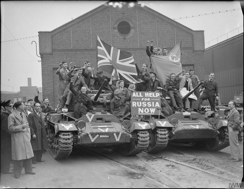 "Factory workers ride on Valentine tanks as they leave a factory in Smethwick. A notice propped on the front of the tanks reads ""All Help for Russia Now"""