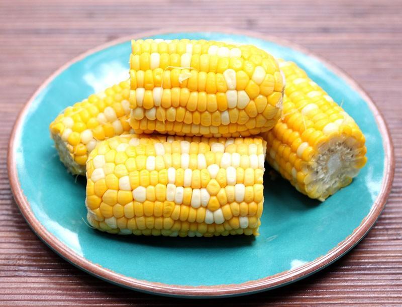 Как быстро сварить кукурузу Отрежьте нижнюю часть початка и поместите кукурузу в микроволновую печь.