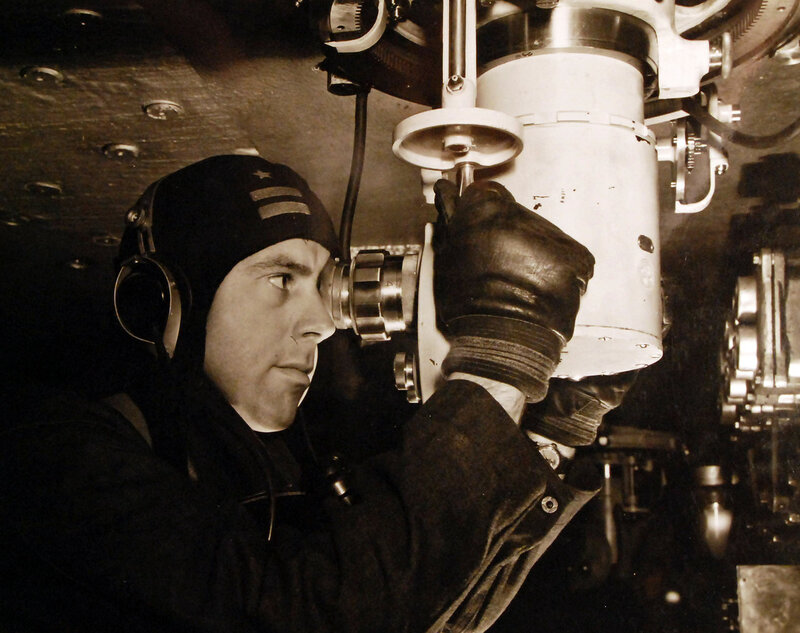 USS Alabama (BB 60). The captain of a gun crew takes a bearing on a target from his individual periscope. Circa December 1942 to January 1943.