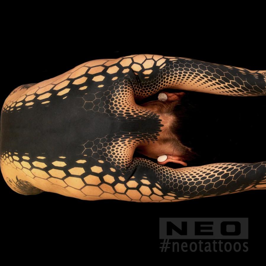 Татуировка, напоминающая змеиную кожу.