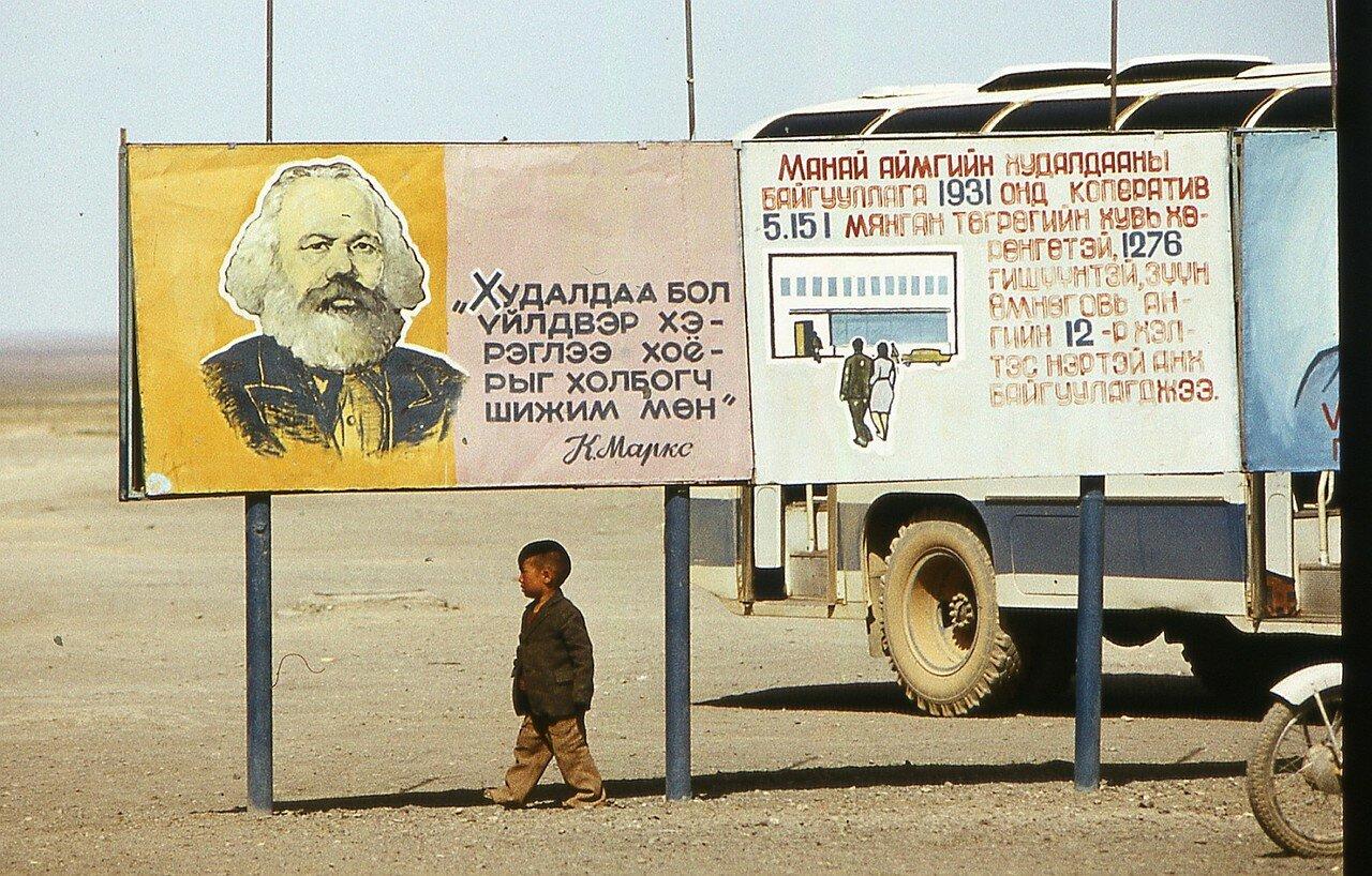 Мальчик в степи под плакатом с Карлом Марксом