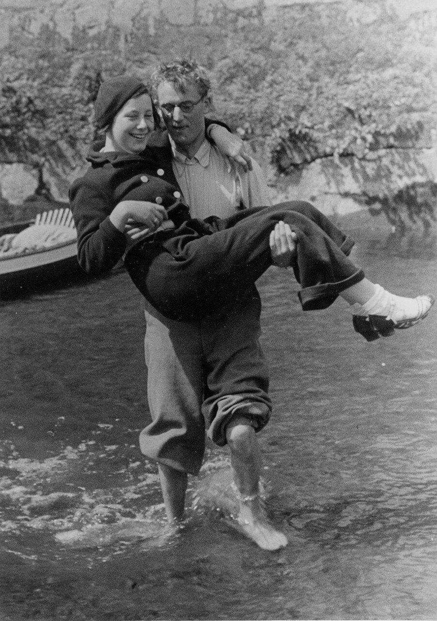 Байдарки на реке Оберальстер. Мужчина переносит женщину на берег