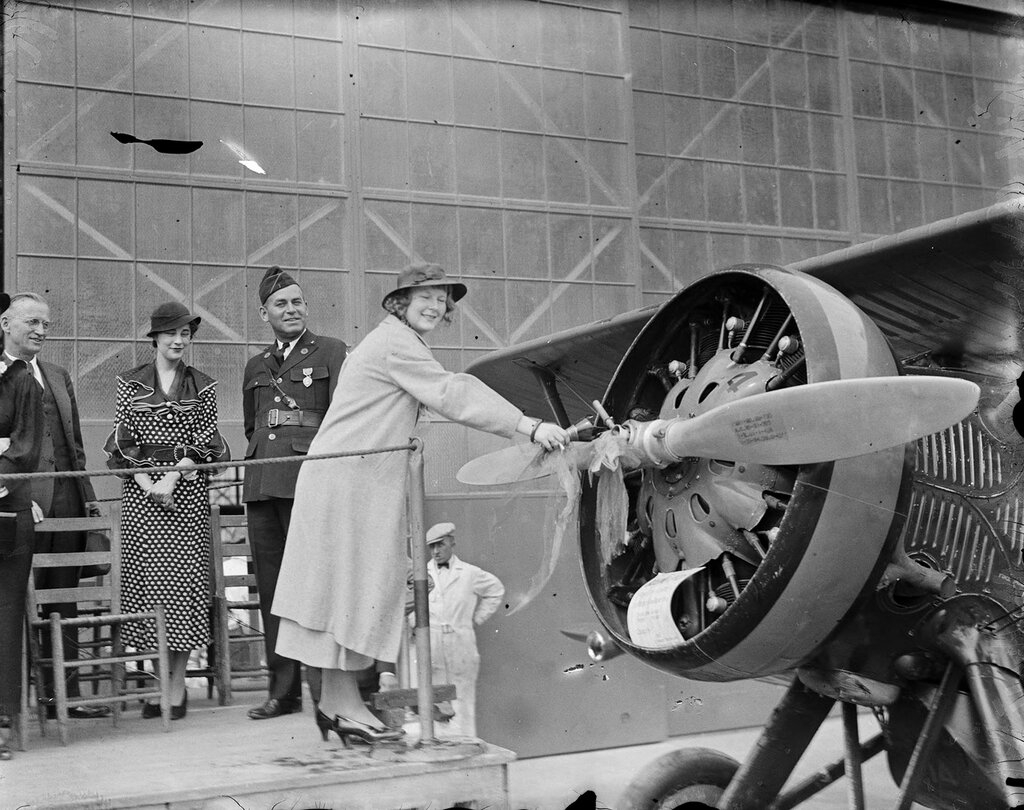 Female christening airplane by breaking a bottle over its propeller as men in uniform and a woman look on in possibly Denver, Colo. between 1930 and 1940.