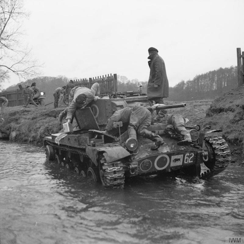 A recovery team works on a Valentine tank of 30th Armoured Brigade, 11th Armoured Division, which broke down in a stream during exercises near Kirkby Lonsdale in Lancashire, 1 April 1942