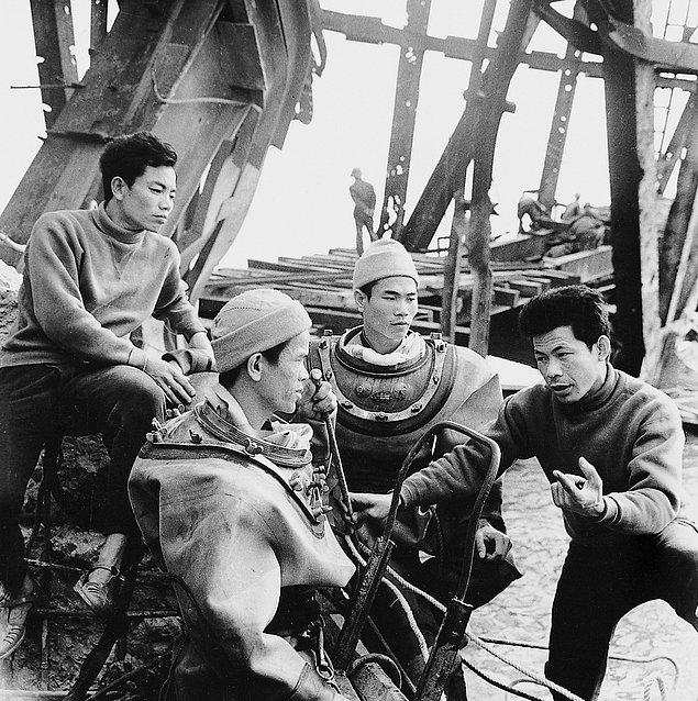 Вьетнамские рабочие разговаривают во время ремонта обрушившегося моста Хам Ронг (1973г.)