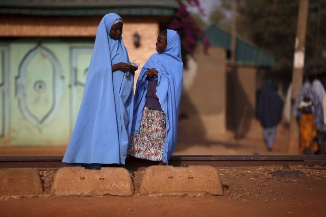 Two girls chat to each other while standing near the railway line in Kaduna state, Nigeria, February