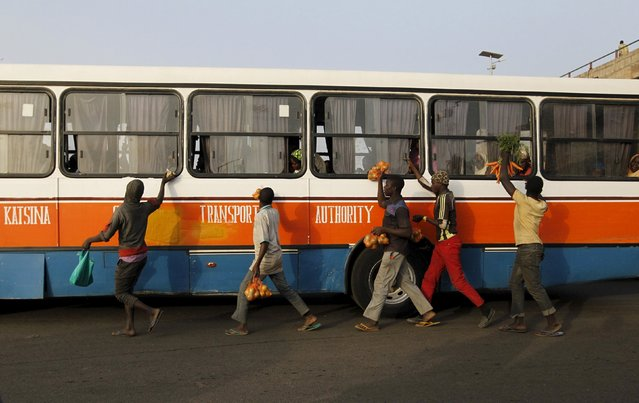 Hawkers run alongside a bus as they try to sell provisions to passengers in Zaria, Kaduna state, Nig