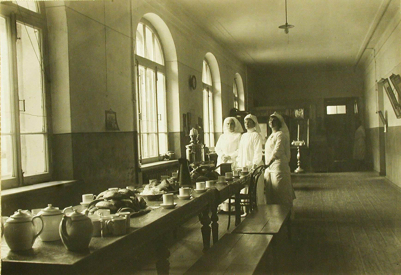 16. Сестры милосердия за приготовлением и сервировкой к чаю стола,оборудованного в одном из коридоров госпиталя