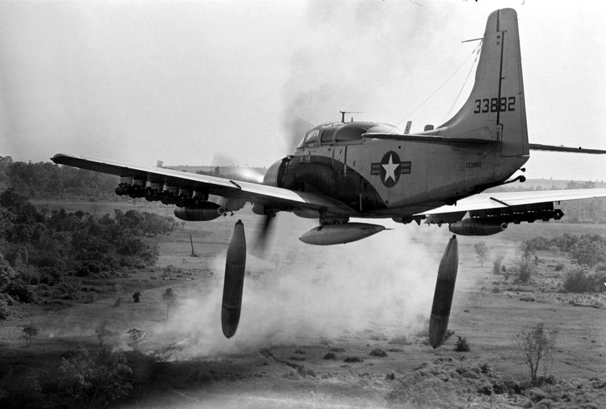 Американский штурмовик Douglas A-1 Skyraider сбрасывает бомбы напалмовые бомбы на позиции войск Северного Вьетнама