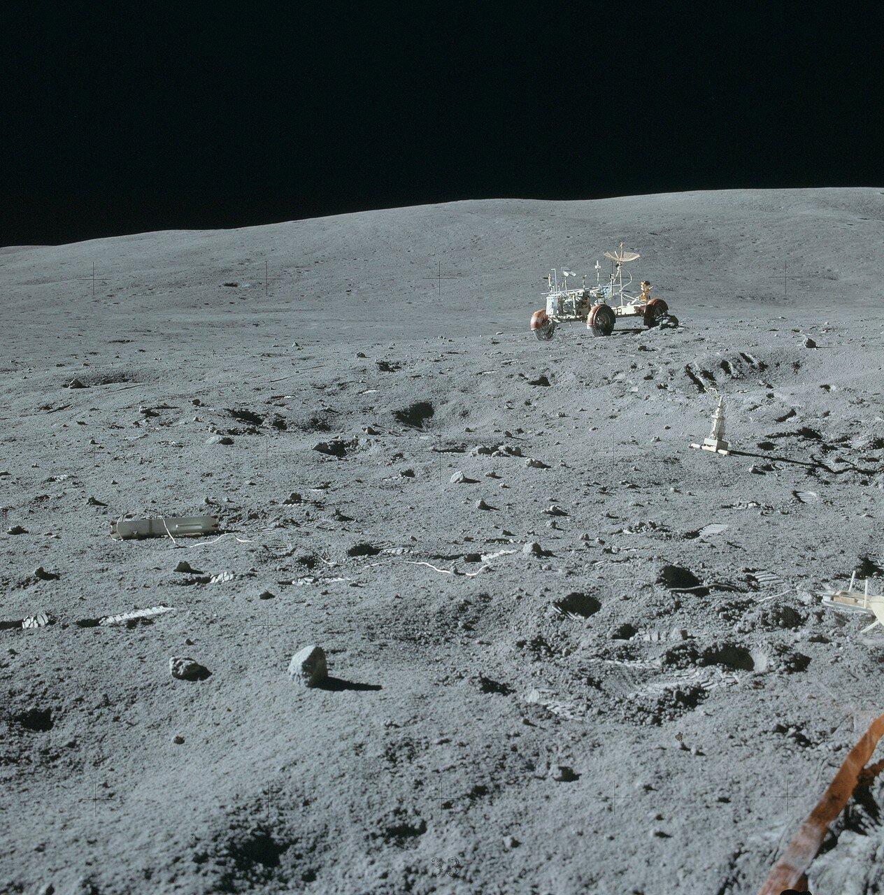До первой геологической остановки у кратера Плам, Янг и Дьюк проехали ровно 2 км, по прямой до лунного модуля от того места было 1,4 км На снимке «Лунный Ровер» у места размещения научных приборов ALSEP. Справа в центре — дрель. Слева — контейнер со свёрл