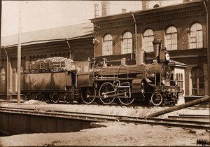Вид паровоза и вагона с лесом на одной из станций.