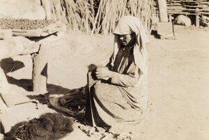 Женщина, обрабатывающая сырую шерсть
