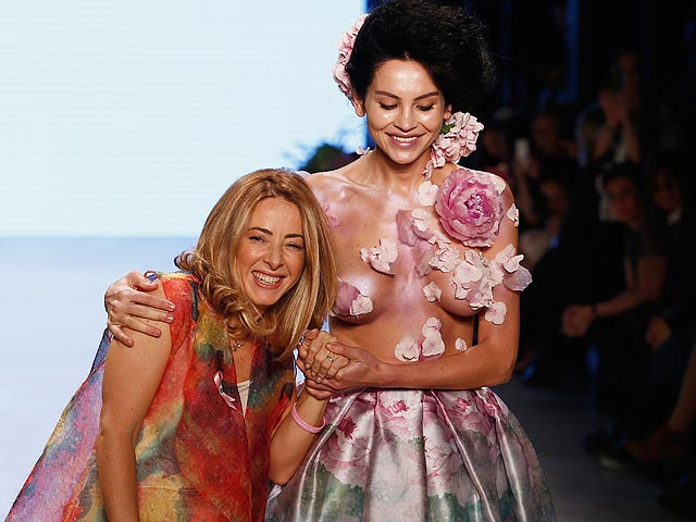 ISTANBUL, TURKEY - OCTOBER 16:  Designer Cigdem Akin and a model walk the show finale of the Cigdem Akin show during Mercedes Benz Fashion Week Istanbul SS15 at Antrepo 3 on October 16, 2014 in Istanbul, Turkey.  (Photo by Andreas Rentz/Getty Images for I