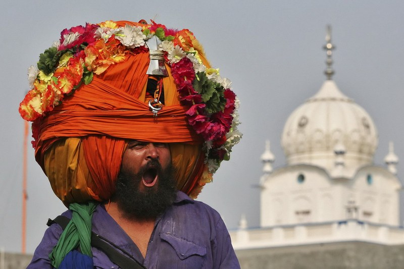 A Nihang or a Sikh warrior, yawns while wearing a turban during a religious procession to mark the Bandi Chhorh Divas in Amritsar