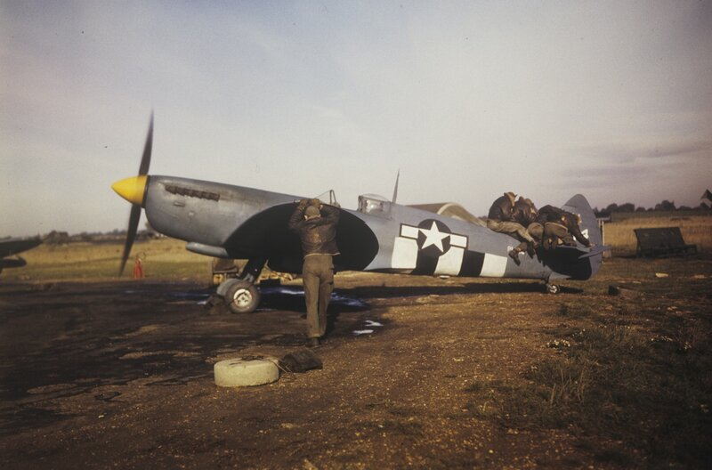 Ground crewmen of the 7th Photographic Reconnaissance Group jump onto the tail of a Spitfire to prevent the aircraft being blown by the wind at Mount farm