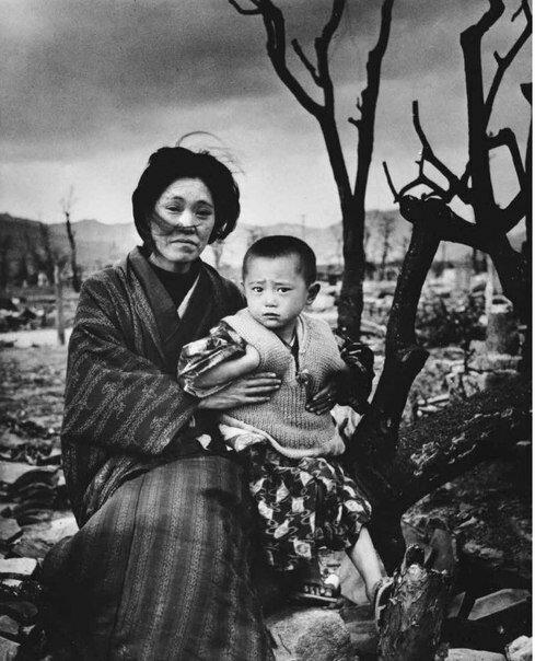 Альфред Эйзенштадт. Мать с ребенком, одетые в национальные костюмы, сидят среди обожженных деревьев и руин Нагасаки. Декабрь 1945.jpg