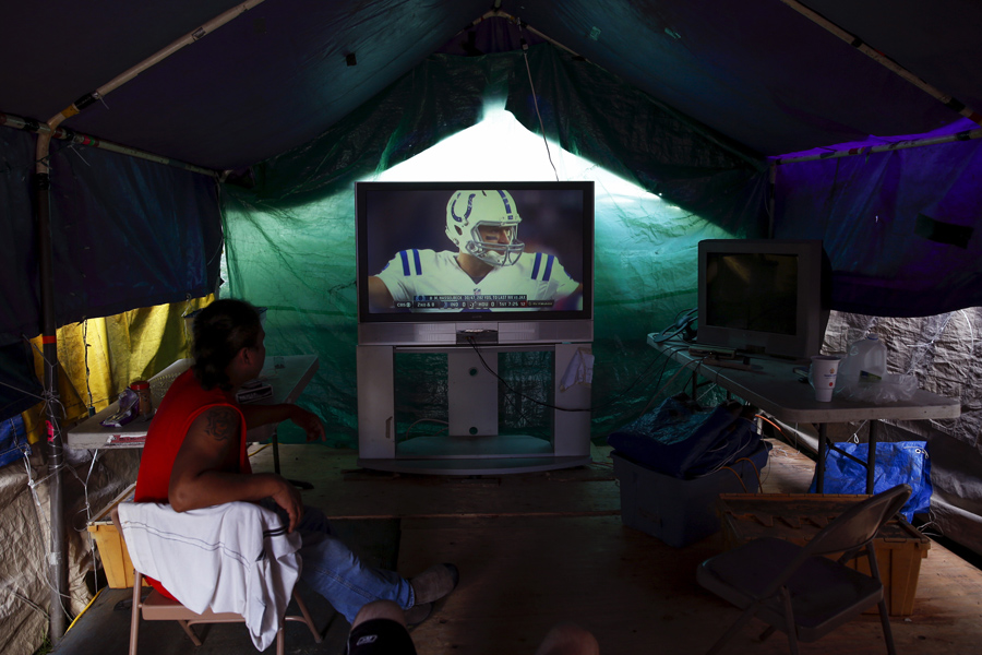 Tent city residents watch an NFL football game in their communal television area at SHARE/WHEEL Tent