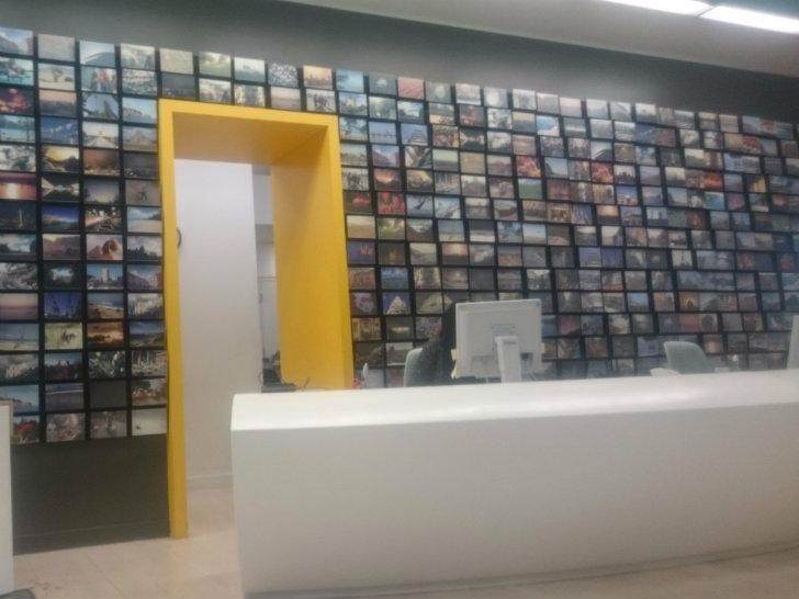 Стена на ресепшене усыпана фотографиями из отпусков сотрудников компании. Сотрудники имеют возможнос