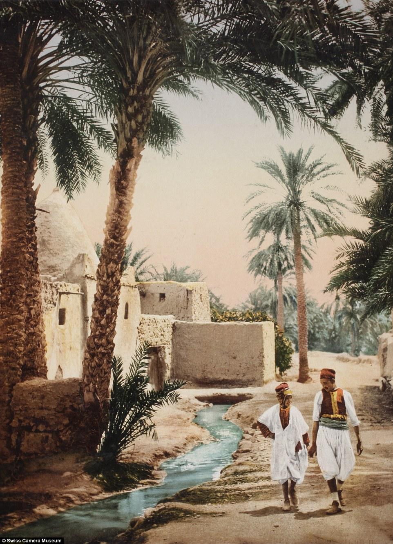 Мужчина с ребенком прогуливаются вдоль ручья, Бискра, Алжир.