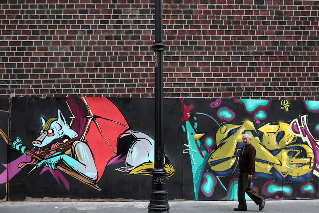 A man walks past graffiti on the closing day of a weekend graffiti festival in Mexico City, Mexico,