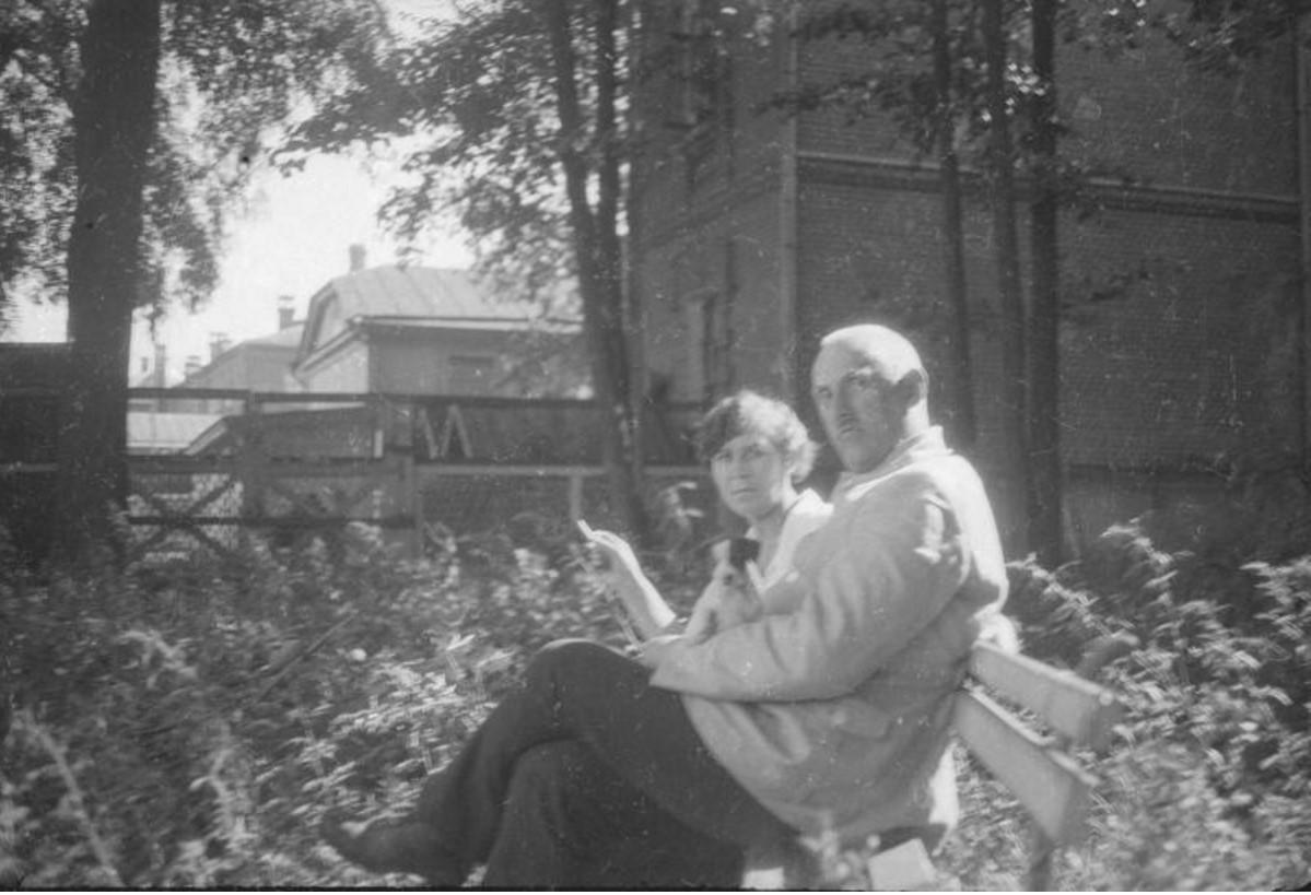 Мужчина и женщина на скамье в палисаднике