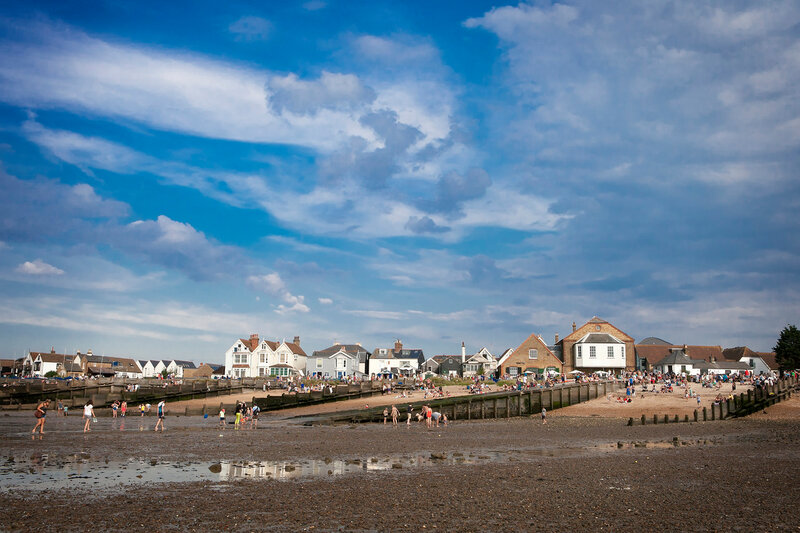 People are looking for crabs and clams on the sea bed at low tide in Whitstable