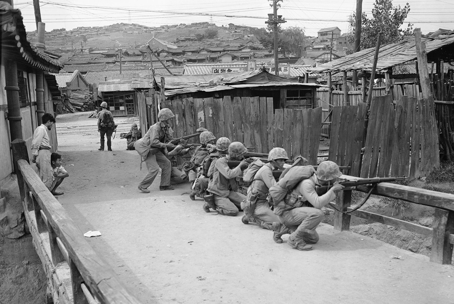 U.S. Marines crouch behind a railing in Seoul on September 27, 1950, as they answer fire from some N