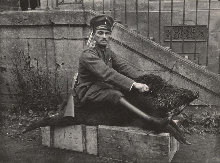 3. Офицер германских ВВС позирует с чучелом кабана рядом с домом, где остановилось его подразделение
