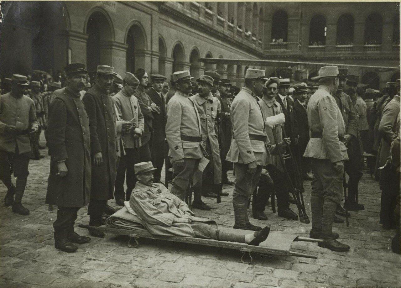 1915. Во дворе Дома Инвалидов. Церемония награждения. Безногий на носилках