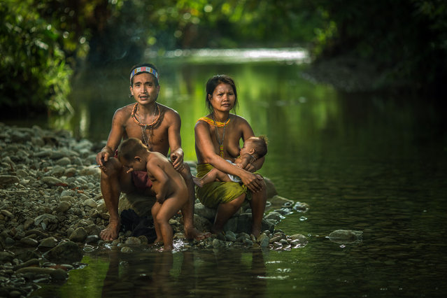 A young Mentawai family sit on the side of the river on July 19, 2014 on the Mentawai Islands, Indon