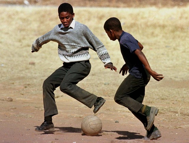 Two school children dreaming of stardom play soccer with an old weathered ball in the yard of a Sowe