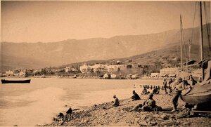 Местные жители на берегу моря у лодок. Ялта