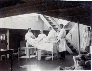 Старший врач И. Х. Дзирне (третий слева), сестра милосердия, младший врач В. П. Ивакин - справа крайний перевязывают  больного в палате № 2 (на перевязочном пункте).