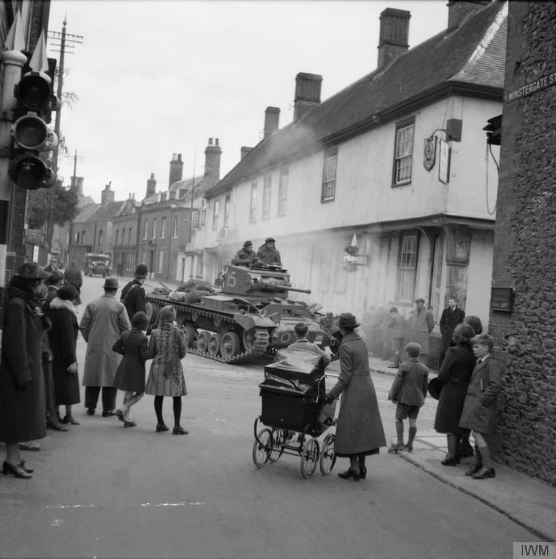 A Valentine tank passes through a village during large-scale manoeuvres near Thetford in Norfolk, 26-28 April 1941