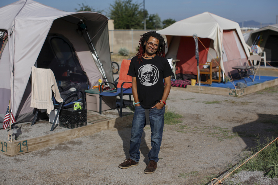 Matt Mercer, a one-time resident of Camp Hope, poses among tents in Las Cruces, New Mexico, on Octob